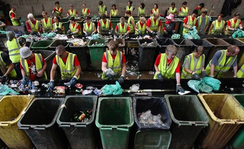 Volunteers in fluorescent jackets stand behind wheelie bins sorting waste at Glastonbury festival